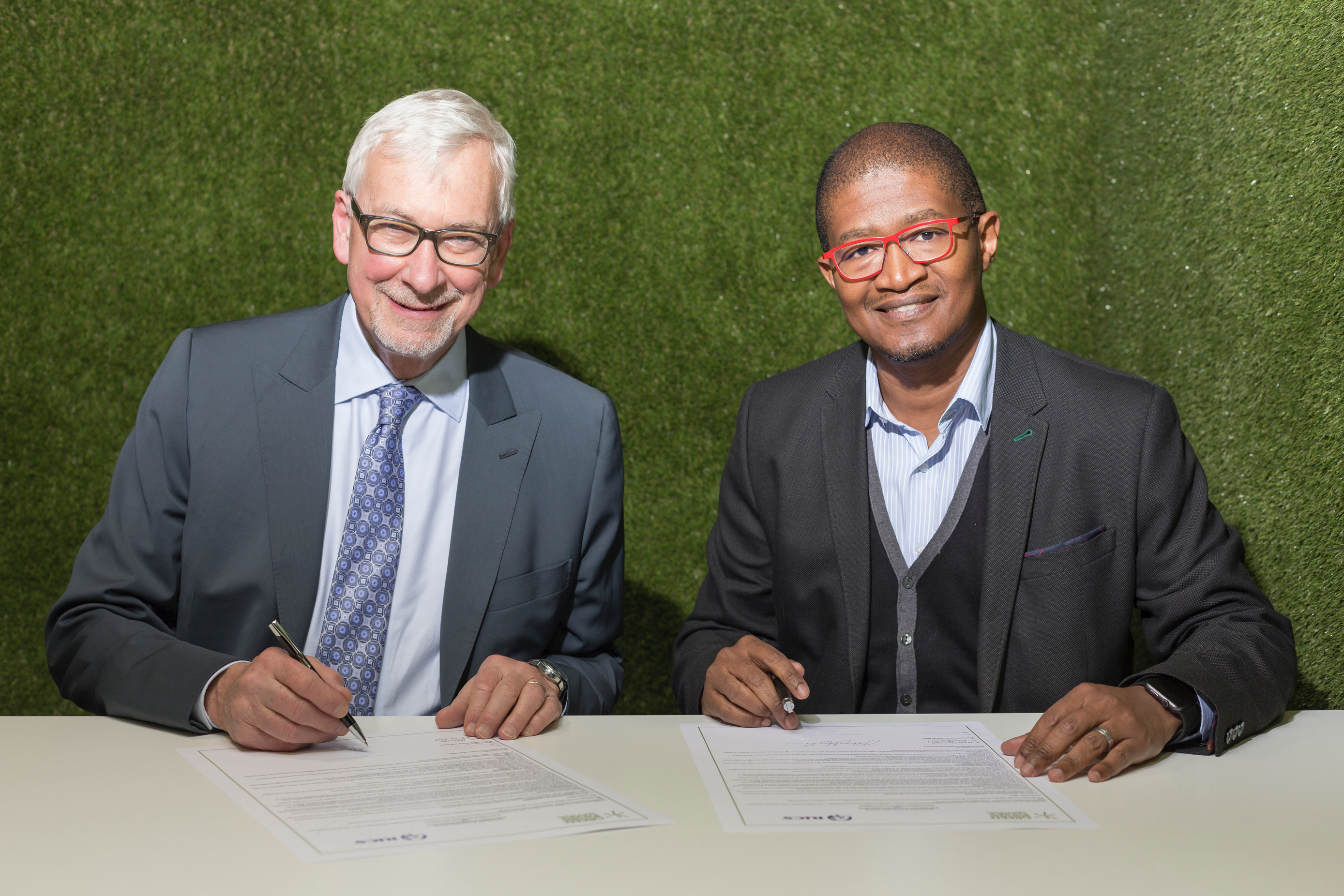 RICS president, John Hughes and GBCSA non-executive deputy chair, Nkosinathi Manzana, sign a memorandum of agreement at the RICS Summit Africa.