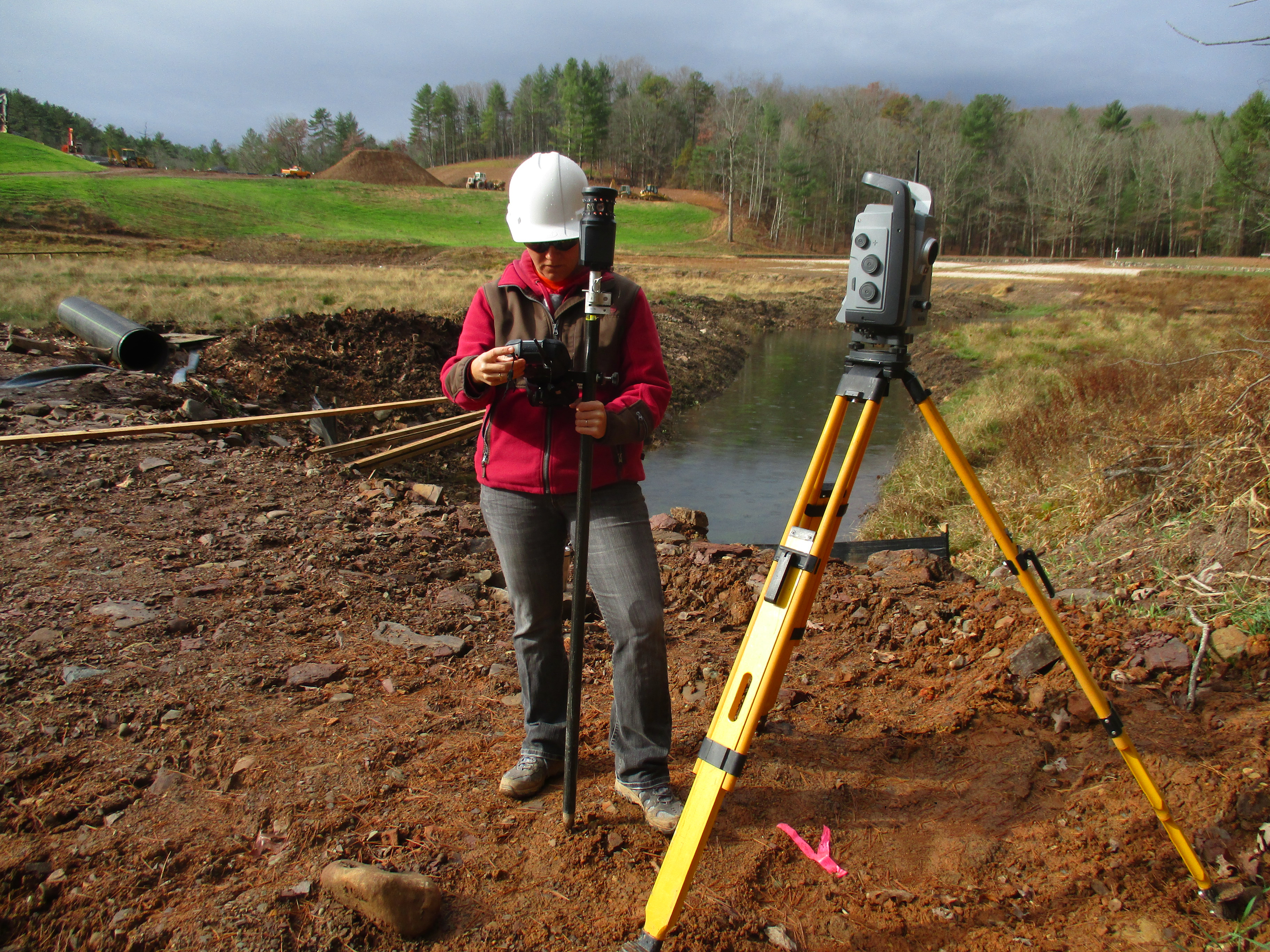 Fig. 2: Evans holds a multitrack prism for the Trimble VX total station to check the surface grade for the dam's rock toe drain.
