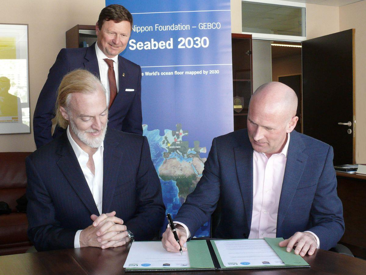 Victor Vescovo (left) and Dr Graham Allen (right) sign the agreement in the presence of Dr Mathias Jonas, secretary general of the International Hydrographic Organization.
